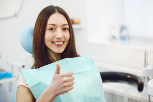 girl-in-dentist-chair-with-thumbs-up-no-braces